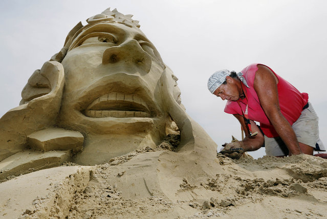 In this July 13, 2012, file photo, Steve Topazio, of Tiverton, R.I., works on his sand sculpture during the annual sand sculpting festival on the beach in Revere, Mass. The 2015 Revere Beach National Sand Sculpting Festival will be held July 24–26, 2015. (Photo by Michael Dwyer/AP Photo)