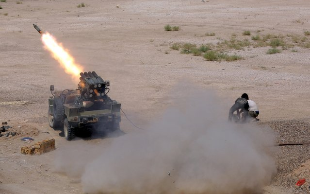 Members of Iraq's Shi'ite paramilitaries launch a rocket towards Islamic State militants in the outskirts of the city of Falluja, in the province of Anbar, Iraq July 12, 2015. (Photo by Reuters/Stringer)