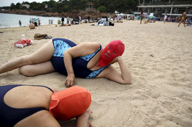 Women wearing face-kini masks lie on a beach to rest in Qingdao, Shandong province, China, June 3, 2015. A pale complexion is highly prized as delicate and feminine in China while dark skin suggests tanning caused by farming the fields or other lowly, outdoor work. (Photo by Reuters/Stringer)