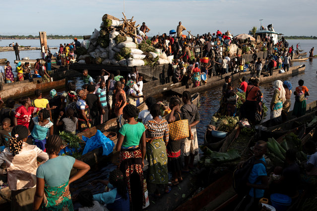 Boats filled with bushmeat arrive at Lingunda market, in Mbandaka, Democratic Republic of the Congo on October 19, 2018. Several hundred men and women wait to buy meat before selling it. (Photo by Thomas Nicolon/Reuters)