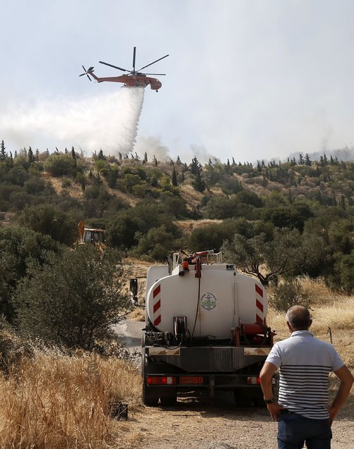 A helicopter drops water over flames on the mountain of Ymittos in Athens, Friday, July 17, 2015. (Photo by Petros Giannakouris/InTime News via AP Photo)