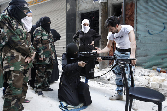 "A female member of the ""Mother Aisha"" battalion receives instruction as she holds a rifle during military training in Aleppo's Salaheddine district, September 19, 2013. (Photo by Loubna Mrie/Reuters)"