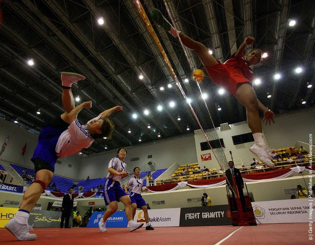 Sepaktakraw: Japan's Yukie Sato (L) blocks a shot from Indonesia during day two of the ISTAF Super Series at the Palembang Sport Convention Center