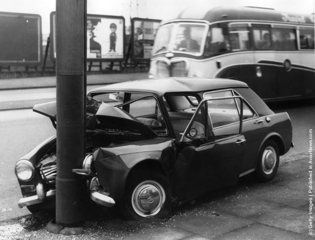 1963: A crashed car by the side of the road in Stratford, east London