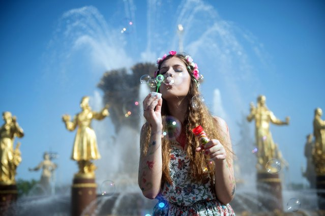 A girl blows soap bubbles during a soap bubble festival Dreamflash in Moscow on May 18, 2014. (Photo by Alexander Utkin/AFP Photo)