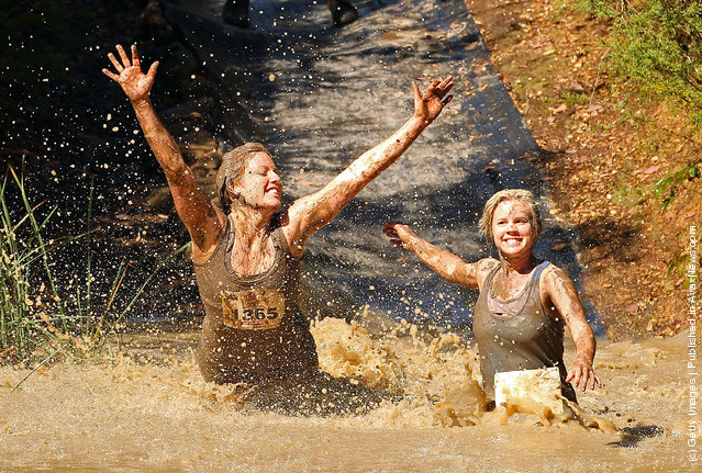 Competitors fall into muddy water as they compete in The Tough Bloke Challenge in Melbourne, Australia