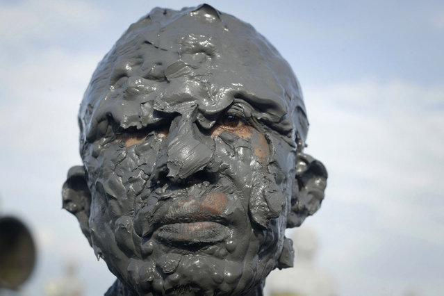 A resident and victim of the mud volcano disaster is covered in mud during a ceremony marking the eighth anniversary of the disaster in Sidoarjo district located in Indonesia's eastern Java island, on May 29, 2014. Lusi, located in the Sidoarjo district of the island of Java, erupted on May 29, 2006 in the middle of a ricefield, in a disaster that displaced some 50,000 people. (Juni Kriswanto/AFP/Getty Images)