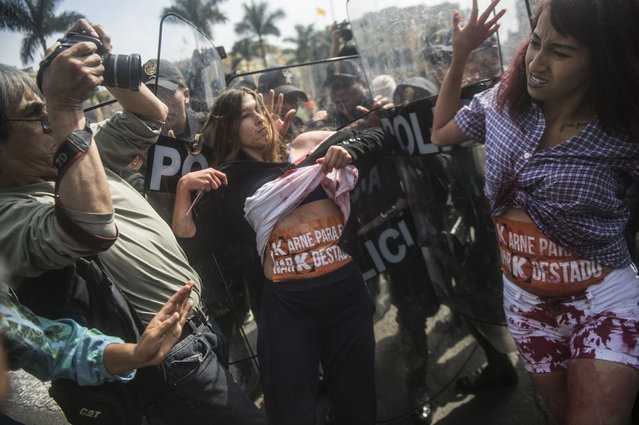 Demonstrators holding a protest against Peru's presidential candidate Keiko Fujimori clash with riot police, in front of the Peruvian Government Palace in Lima on May 26, 2016. According to a recent poll, Fujimori, the divisive daughter of Peru's jailed ex-president Alberto Fujimori, has a firm lead -of 46 percent- for the June 5 run-off election against center-right economist Pedro Pablo Kuczynski, who has 38.9 percent. (Photo by Ernesto Benavides/AFP Photo)