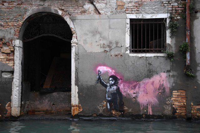 """The artwork by street artist Banksy, that portrays a migrant child wearing a lifejacket and holding a neon pink flare, is pictured after an exceptional overnight """"Alta Acqua"""" high tide water level, on November 13, 2019 in Venice. Venice was hit by the highest tide in more than 50 years late November 12, with tourists wading through flooded streets to seek shelter as a fierce wind whipped up waves in St. Mark's Square. (Photo by Marco Bertorello/AFP Photo)"""