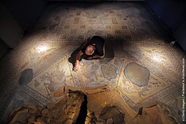 David Rawcliffe, house and monument steward at the National Trust's Chedworth Roman Villa cleans a Roman mosiac in the new environmentally-controlled conservation shelter near Cirencester, England