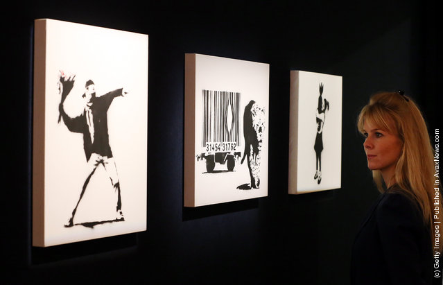 Employee Leonora Oldfield looks at Banksy's (L-R) 'Love is in the Air', 'Leopard and Barcode' and 'Bomb Hugger' at Bonhams