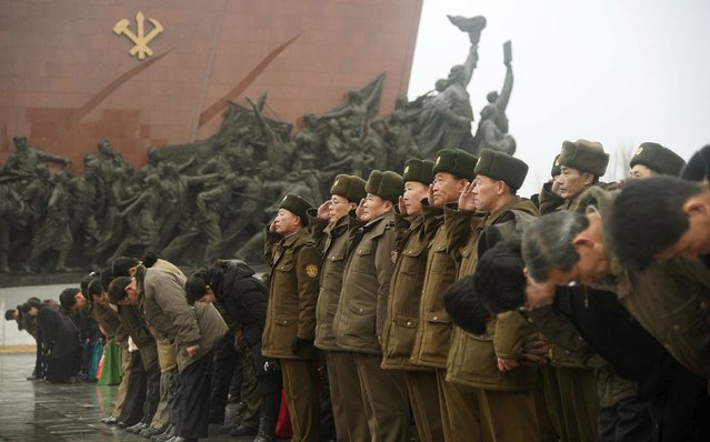 North Korean soldiers salute as others bow to bronze statues (not pictured) of North Korea's late founder Kim Il-sung and late leader Kim Jong Il at Mansudae in Pyongyang, in this photo provided by Kyodo February 16, 2015, on the birth anniversary of North Korea's late leader, Kim Jong Il. (Photo by Reuters/Kyodo News)