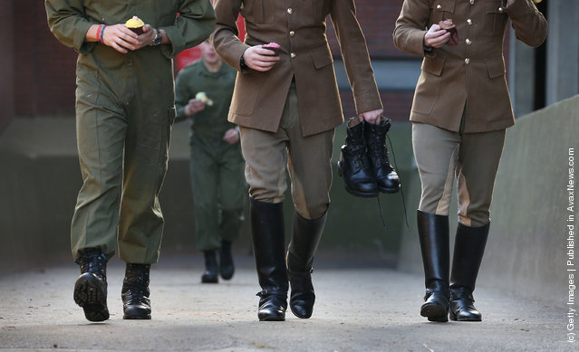 Members of  The Household Cavalry Mounted Regiment (HCMR) carry cupcakes for breakfast and a pair of boots before parade at Hyde Park Barracks
