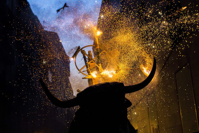 "A flaming fake bull known as a ""Toro de fuego"" runs after revelers during San Fermin festival in Pamplona, Spain, Monday, July 13, 2015. Revelers from around the world arrive in Pamplona every year to take part in some of the eight days of the running of the bulls. (Photo by Andres Kudacki/AP Photo)"