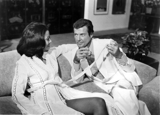 """Actor Roger Moore as James Bond and actress Emily Bolton as Manuela on set for the United Artist movie """"Moonraker"""" in 1979. (Photo by Michael Ochs Archives/Getty Images)"""