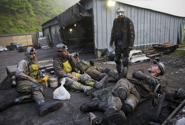 In this Thursday, May 12, 2016 photo, coal miner Scottie Stinson, front, drives a man trip as he and fellow workers head into an underground mine less than 40-inches high to start their shift in Welch, W.Va. (Photo by David Goldman/AP Photo)