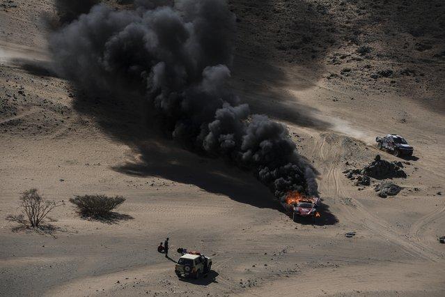 The car of driver Dumas Romain and co-driver Winocq Alexandre, of France, burns during stage one of the Dakar Rally, between Jiddah and Al Wajh, Saudi Arabia, Sunday, January 5, 2020. (Photo by Frank Fife/Pool Photo via AP Photo)