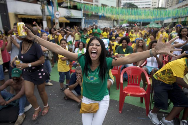 Brazil soccer fans celebrate after their team scored a penalty shot against Chile as they watch the World Cup round of 16 match on TV outside the Vai Vai Samba school in Sao Paulo, Brazil, Saturday, June 28, 2014. Brazil won 3-2 on penalties. (Photo by Dario Lopez-Mills/AP Photo)