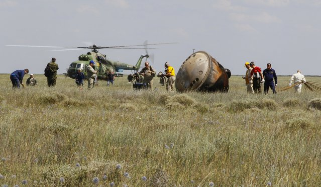 Search and rescue team members work at the site of landing of the Soyuz TMA-19M capsule carrying NASA's Tim Kopra, Tim Peake of the European Space Agency and Russian agency Roscosmos' Yuri Malenchenko near the town of Dzhezkazgan, Kazakhstan, Saturday, June 18, 2016. (Photo by Shamil Zhumatov/Pool Photo via AP Photo)