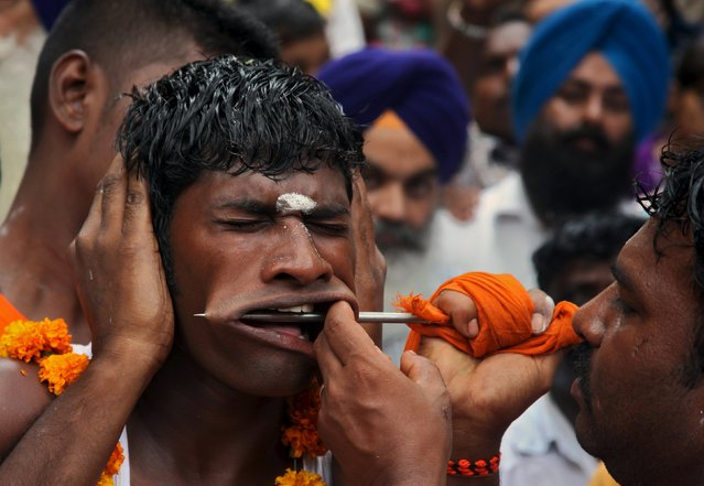 """A Hindu devotee gets his cheeks pierced as he takes part in an annual religious procession called """"Shitla Mata"""" in Chandigarh, India August 9, 2015. Hindu devotees subject themselves to painful rituals during the religious procession to demonstrate their faith and as a penance to the deity at a temple dedicated to the goddess Shitla. (Photo by Ajay Verma/Reuters)"""