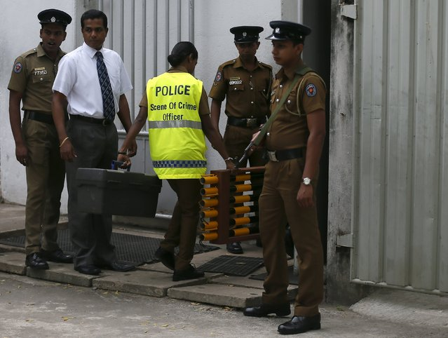 A police scene of crime officer carries equipment into a cemetery after the Colombo Additional Magistrate allowed the exhumation of the body of rugby player Wasim Thajudeen in Colombo August 10, 2015. According to initial reports, Thajudeen's body was found in a burnt-out car wreck and his death was ruled an accident. But police last month requested that the case be reopened after saying they have uncovered new evidence, local media reported. (Photo by Dinuka Liyanawatte/Reuters)