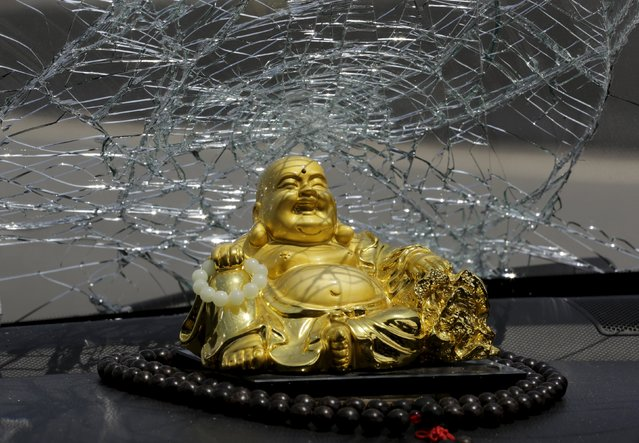 A figurine of Maitreya Buddha is seen under a broken car window,  near the site of the explosions at the Binhai new district, Tianjin, August 13, 2015. Officials from the northeast Chinese city of Tianjin, where two huge blasts in warehouses containing toxic chemicals and gas killed 44 people, said just a week ago they had discussed tightening safety standards with companies at the port. (Photo by Jason Lee/Reuters)