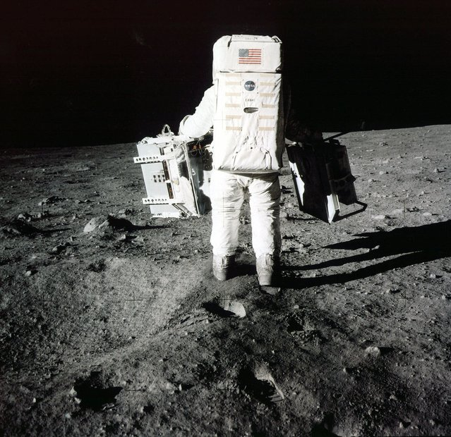 "In this July 20, 1969 file photo provided by NASA, Edwin ""Buzz"" Aldrin carries scientific experiments to a deployment site south of the lunar module Eagle during the Apollo 11 mission. One experiment involved the inner composition of the moon, and another tried to determine the exact distance from Earth. Aldrin, 84, is asking everyone to remember where they were when he and Neil Armstrong became the first humans to walk on the moon and to share their memories online. (Photo by AP Photo/NASA)"