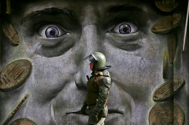 In this Monday, July 24, 2017 photo, a police officer walks in front of a mural during a protest demanding an end to the current pension fund system, in Santiago, Chile. Protesters say the government pension system robs retirees of fair pension payments, and are demanding a new social security system with higher payments. (Photo by Esteban Felix/AP Photo)
