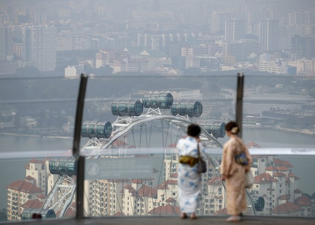 Women wearing kimonos look at the Singapore Flyer shrouded by haze near the central business district in Singapore August 21, 2015. The 3-hour Pollutants Standards Index or PSI reading hit 78 at 5pm on Friday, according to the National Environment Agency. (Photo by Edgar Su/Reuters)