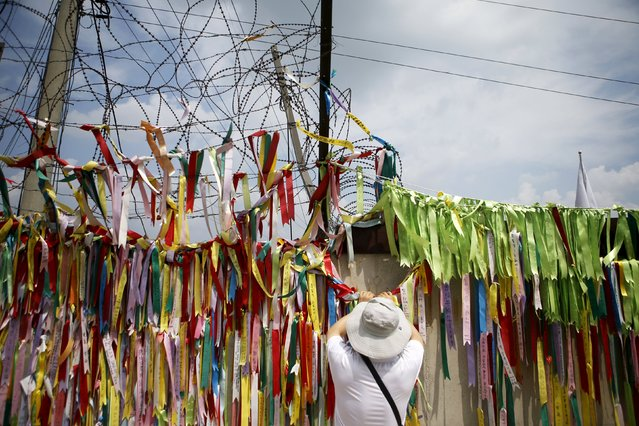 A tourist hangs a ribbon bearing messages wishing the unification of the two Koreas on a barbed-wire fence at the Imjingak pavilion near the demilitarized zone separating the two Koreas in Paju, South Korea, August 22, 2015. South Korea stands ready to respond to further provocations from North Korea, the presidential Blue House said on Saturday, as an ultimatum loomed for Seoul to halt anti-Pyongyang propaganda broadcasts by late afternoon or face military action. (Photo by Kim Hong-Ji/Reuters)