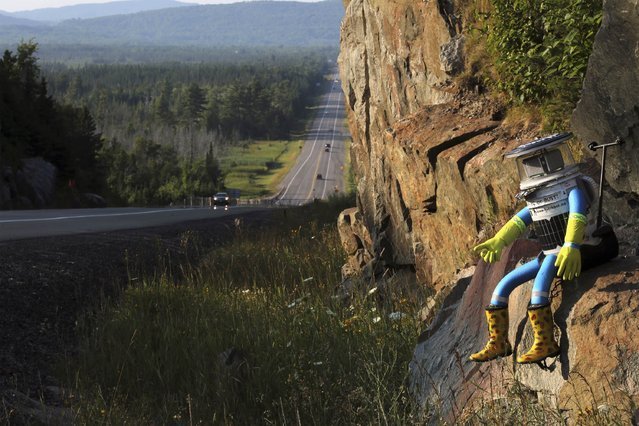 The hitchBOT is seen posed next to Highway 17 north of Sault Ste. Marie, Ontario, and a portion of the Trans-Canada Highway August 5, 2014. The hitch-hiking robot is now at the halfway point in its journey across Canada. (Photo by Kenneth Armstrong/Reuters)