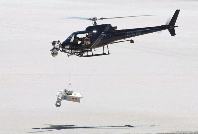 """This test for the radar system to be used during the August 2012 descent and landing of NASA Mars rover Curiosity mounted an engineering test model of the radar system onto the nose of a helicopter. During the final stage of descent, NASA's Mars Science Laboratory mission will use a """"sky crane"""" maneuver to lower Curiosity on a bridle from the mission's rocket-powered descent stage. The descent stage will carry Curiosity's flight radar. This test on May 12, 2010, at NASA Dryden Flight Research Center, in Edwards, California, included lowering a rover mockup on a tether from the helicopter to assess how the sky crane maneuver will affect descent-speed determinations by the radar. (Photo by NASA)"""