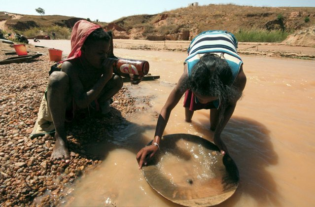 A woman washes earth dug out from local mines in the hope of finding sapphires in the town of Sakaraha in this September 12, 2007 file photo. With woeful air links hobbling tourism and power outages holding back its textiles industry, the former French colony's economic recovery after years of political turmoil hinges on the revival of its mining sector. But without permits, most miners are unable to raise cash on stock markets or get loans to keep their projects alive. (Photo by Jasleen Sethi/Reuters)