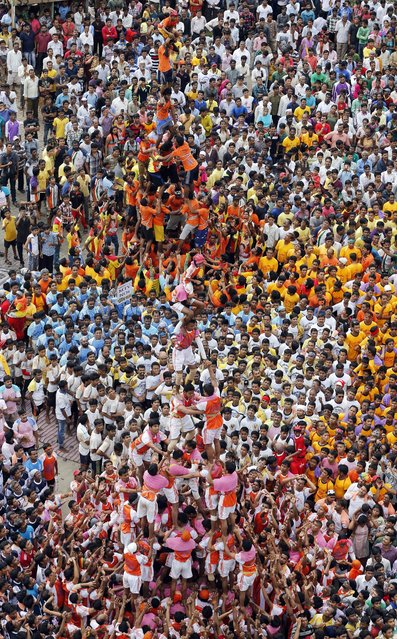 """People watch as Indian youth form human pyramids to break the """"Dahi handi"""", an earthen pot filled with curd, an integral part of celebrations to mark Janmashtami in Mumbai, India, Monday, August 18, 2014. (Photo by Rafiq Maqbool/AP Photo)"""