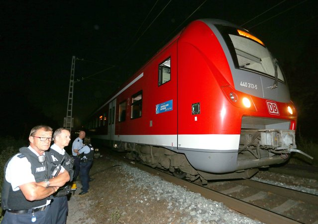 Police stand by the regional train on which a man allegedly wielding an axe attacked passengers in Wuerzburg, Germany, 18 July 2016. Reports state that a man allegedly wielding an axe injured multiple passengers on a regional train in Wuerzburg. The attacker was shot by police. (Photo by Karl-Josef Hildenbrand/EPA)