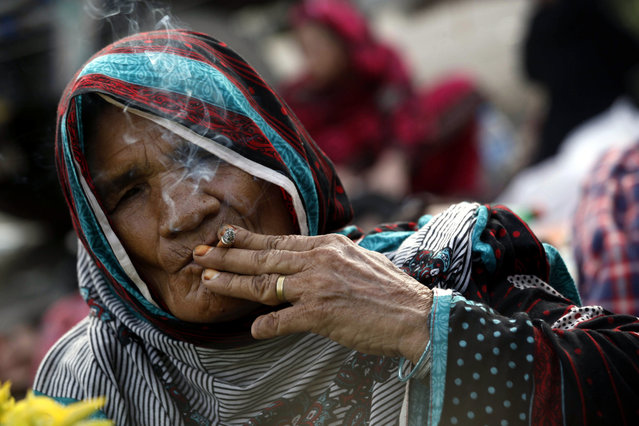 A supporter of Tahirul Qadri, a Pakistani-Canadian cleric, smokes as she continues her sit-in protest for the sixth day in Islamabad, Pakistan, August 20, 2014. Thousands of anti-government protesters led by Imran Khan and Canada-based cleric Tahirul Qadri marched towards the red zone amid fears that a prolonged confrontation might lead to a military coup a year after the country's first democratic transfer of power. (Photo by Bilawal Arbab/EPA)