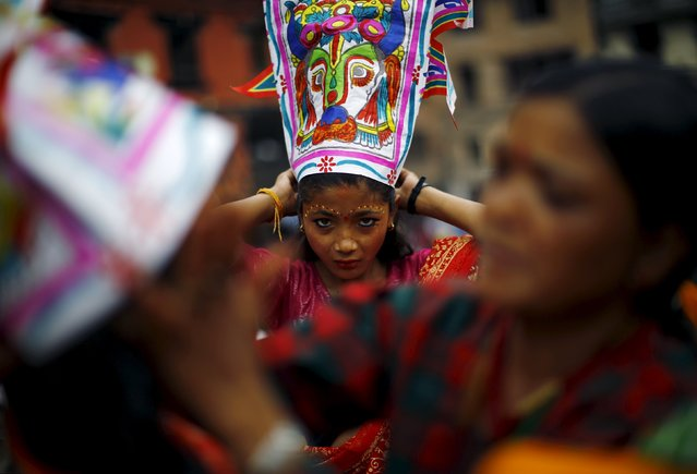 A girl depicting a holy cow gets ready to take part in a parade to mark the Gaijatra Festival, also known as the festival of cows, in Kathmandu, Nepal August 30, 2015. (Photo by Navesh Chitrakar/Reuters)