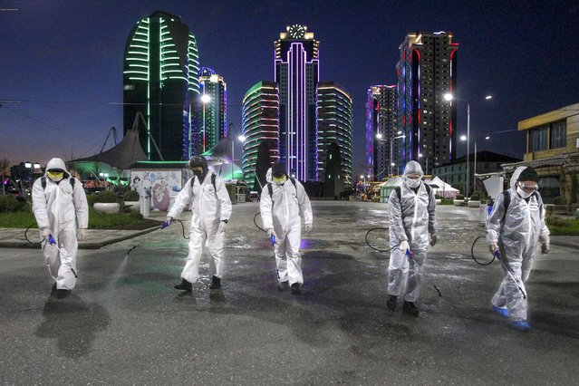 Municipal workers wearing protective suits spray disinfectant in an area in the center of Grozny, Russia, Monday, April 6, 2020. Ramzan Kadyrov, strongman leader of Russia's province of Chechnya, has taken extreme measures to fight the spread of the new coronavirus in the region, vowing Monday not to let anyone who is not a formal resident of Chechnya into the area. (Photo by Musa Sadulayev/AP Photo)