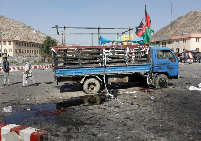 A damaged truck was hit by a suicide attack is parked at the site of blast in Kabul, Afghanistan July 23, 2016. (Photo by Omar Sobhani/Reuters)