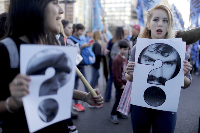 Demonstrators hold pictures of Santiago Maldonado, right, and Julio Lopez, left, during a protest to demand their appearance in Buenos Aires, Argentina, Monday, September 18, 2017. Julio Lopez disappeared 11 years ago, shortly after being a witness on a trail on crimes against humanity and Santiago Maldonado, who disappeared Aug. 1, 2017. (Photo by Natacha Pisarenko/AP Photo)