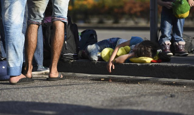 A child of a migrant sleeps on the ground outside the main railway station in Munich, Germany, September 1, 2015. (Photo by Lukas Barth/Reuters)