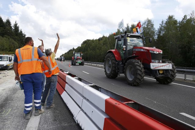 Workers wave to French farmers from Lorraine region as they drive their tractors on the A4 motorway in the Champagne-Ardenne region, eastern France, September 2, 2015. Hundreds of tractors were heading towards Paris for a protest due to take place on Thursday where French farmers will call for more help with low prices and high costs in the European Union's largest agricultural producer country. (Photo by Jacky Naegelen/Reuters)