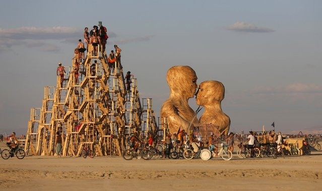 "People interact with art installations during the Burning Man 2014 ""Caravansary"" arts and music festival in the Black Rock Desert of Nevada August 26, 2014. (Photo by Jim Urquhart/Reuters)"