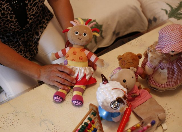 Hu, whose son Zhao's whole family was onboard Malaysia Airlines Flight MH370 which disappeared on March 8, 2014 shows her missing granddaughter's dolls during an interview with Reuters in Beijing July 24, 2014. Hu said she had thought of committing suicide. She could not go back home for a while after the incident because she was afraid of entering the empty house which had been full of her 3 year-old granddaughter's lovely smile. (Photo by Kim Kyung-Hoon/Reuters)