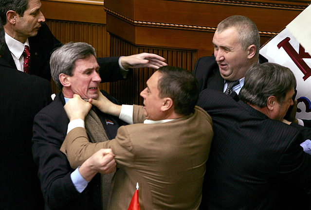 Deputies of Ukraine's parliament fight prior the annuel speech by Ukrainian President Viktor Yushchenko at the parliament in Kiev 09 February, 2006. The fighting was provoked by the Communists who wanted to attach an anti-president placard to the speakers platform. (Photo by Sergei Supinsky/AFP Photo)