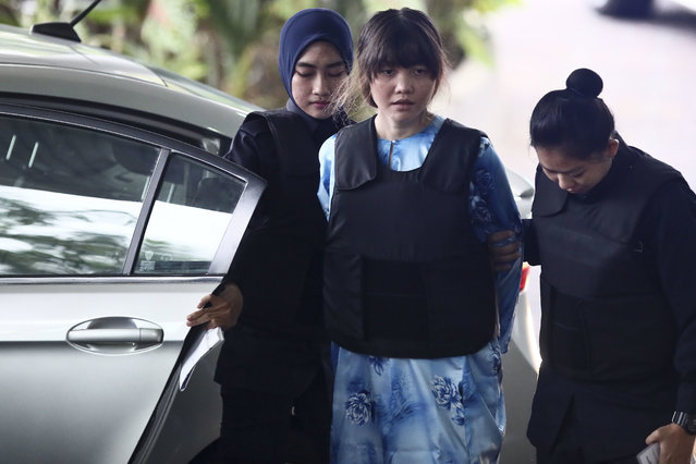 Vietnamese Doan Thi Huong, center, is escorted by police officers as she arrives for a court hearing at Shah Alam court house in Shah Alam, outside Kuala Lumpur, Malaysia, Thursday, October 12, 2017. Security camera videos showed Wednesday Kim Jong Nam, the estranged half brother of North Korea's leader, being attacked at a Malaysian airport and the two suspects, including Doan, hurrying away afterward have been presented at their murder trial. (Photo by Sadiq Asyraf/AP Photo)