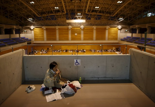 An evacuee from an area flooded by the Kinugawa river, caused by typhoon Etau, uses her mobile phone at Ishige Sports Park acting as an evacuation center in Joso, Ibaraki prefecture, Japan, September 10, 2015. (Photo by Issei Kato/Reuters)