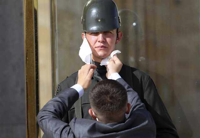 A man wipes the face of a Turkish soldier wearing a face mask for protection against the new coronavirus, before a ceremony at the mausoleum of Mustafa Kemal Ataturk, the founder of modern Turkey, in Ankara, Turkey, Tuesday, May 19, 2020. This year's limited ceremony is marking the 101st anniversary of the start of Turkey's War of Independence under the leadership of the young Ottoman army general. (Photo by Burhan Ozbilici/AP Photo)