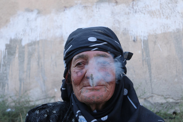 A woman smokes as she rests after she was evacuated with others by the Syria Democratic Forces fighters from an Islamic State-controlled neighbourhood of Manbij, in Aleppo Governorate, Syria, August 12, 2016. (Photo by Rodi Said/Reuters)