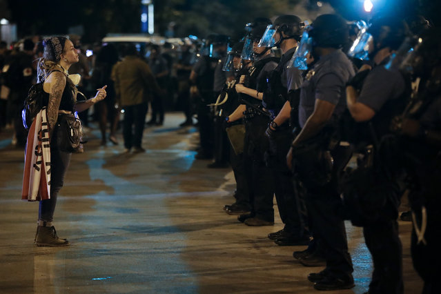 A protester confronts a line of police in riot gear near midnight Wednesday night, June 3, 2020, in Kansas City, Mo., after a unity march to protest against police brutality following the death of George Floyd, who died after being restrained by Minneapolis police officers on May 25. (Photo by Charlie Riedel/AP Photo)